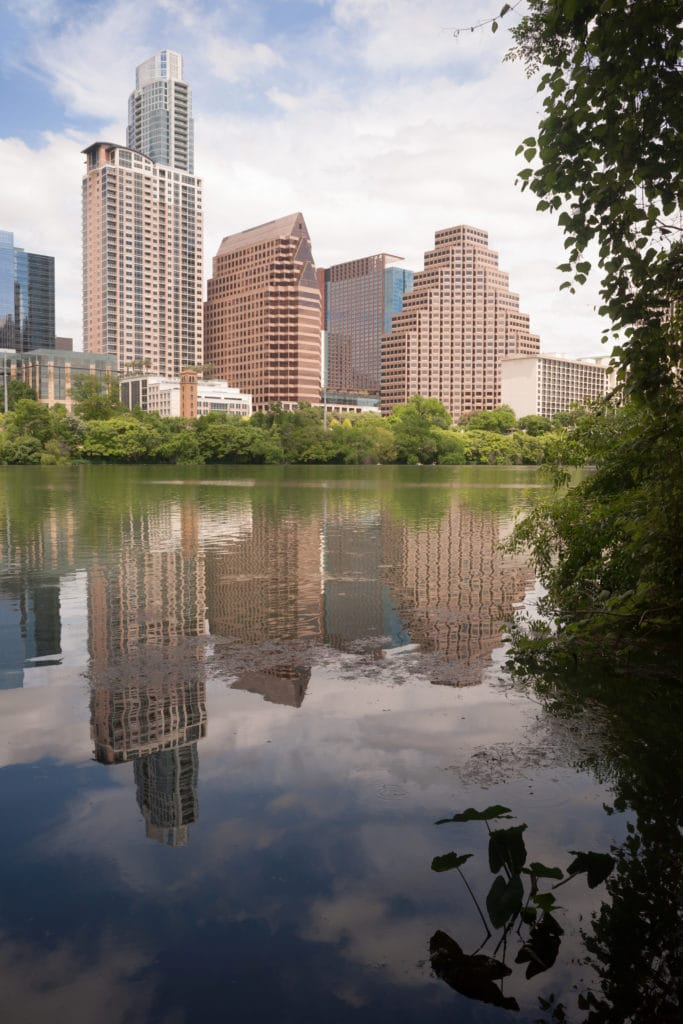 The sun is setting on buildings reflected in the Colorado River as it meanders through Austin, Texas.